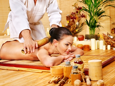 beauty parlour: Young woman getting bamboo massage. Male therapist.