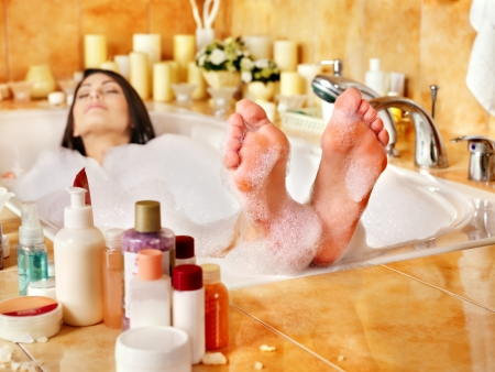lying in bathtub: Woman relaxing at water in bubble bath.