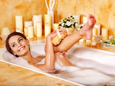 lying in bathtub: Young woman wash leg in bathtube.