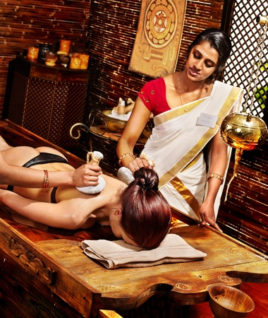 Woman having Ayurveda massage with pouch of rice. photo