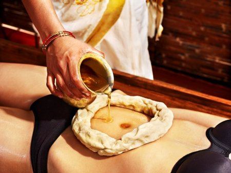 panchakarma: Young woman having stomach Ayurveda spa treatment. Stock Photo