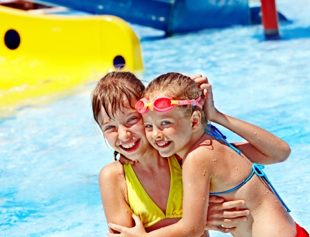 Children on water slide at aquapark. Summer holiday. Stock Photo
