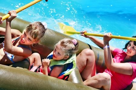 aqua park: Family with children  ride  rubber boat at  swimming pool .