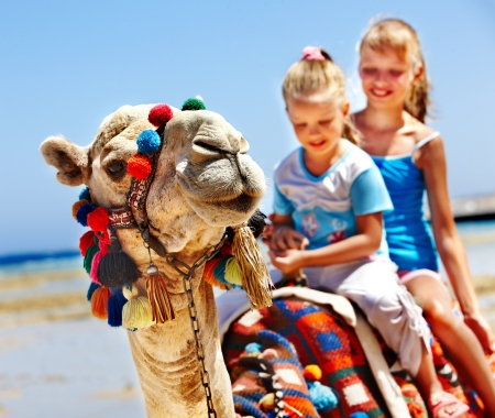Tourists children riding camel  on the beach of  Egypt. Sharpness on a camel. photo