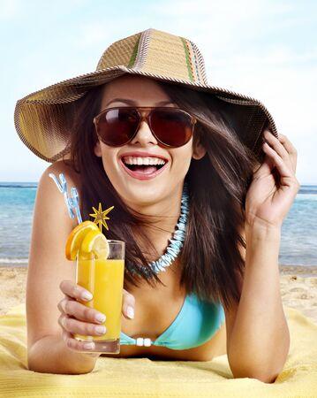 Woman in bikini drinking alcohol coctail through a straw.