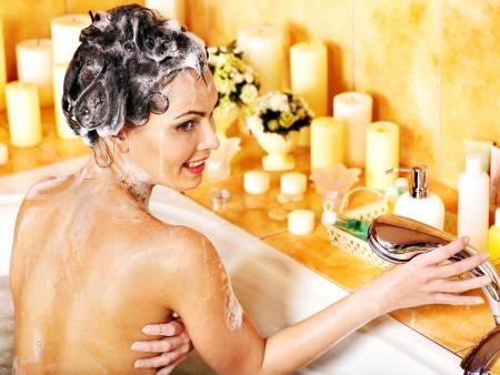 mujer bañandose: La mujer se lava la cabeza en el baño de casa. Foto de archivo