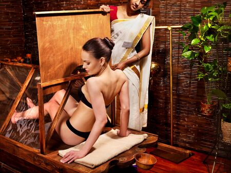 Woman having Ayurvedic sauna treatment. photo