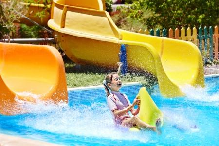 aqua park: Child on water slide at aquapark. Summer holiday..