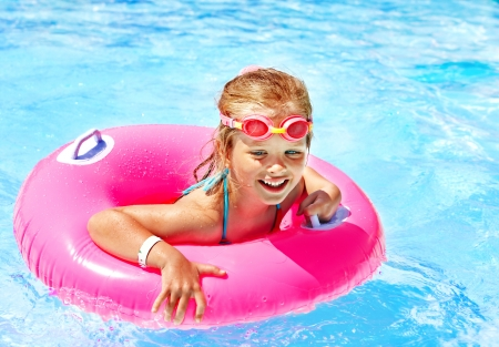 kids swimming pool: Children sitting on inflatable ring in swimming pool. Stock Photo