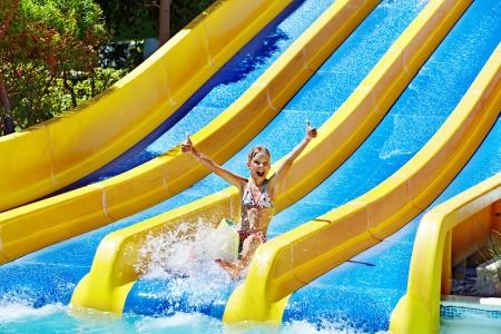 WATER SLIDE: Children on water slide at aquapark. Summer holiday. Stock Photo