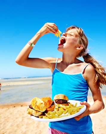 burger and fries: Child eating fast food at beach outdoor.