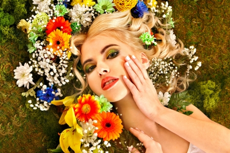 Woman with flower hairstyle lying on grass photo