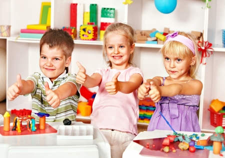 playschool: Group of children  in preschool thumb up. Stock Photo