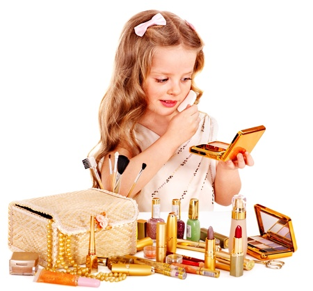 Child cosmetics. Little girl applying make up. photo