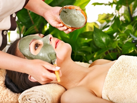 Woman with clay facial mask in beauty spa. photo