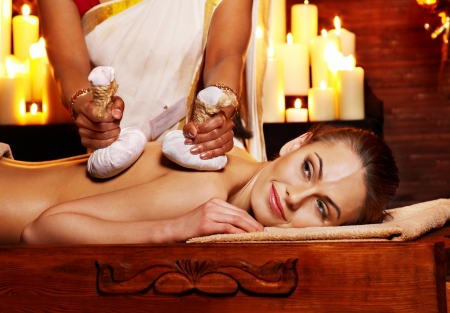 herbal massage ball: Woman having ayurvedic massage with pouch of rice.