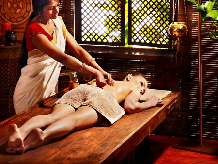 body massage: Young woman having oil Ayurveda spa treatment. Stock Photo