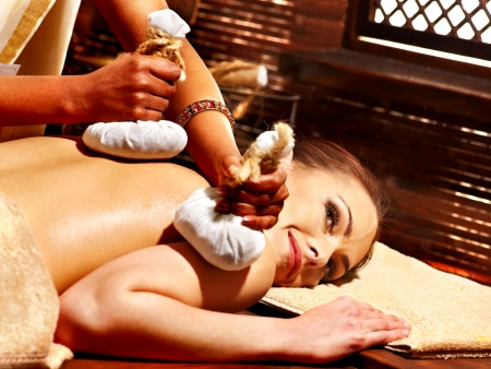 Woman having Ayurveda massage with herbal ball. photo