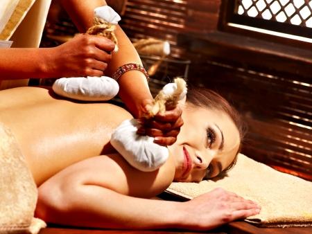 herbal massage ball: Woman having Ayurveda massage with herbal ball.