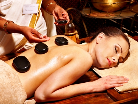 Young woman having Ayurveda stone massage. photo
