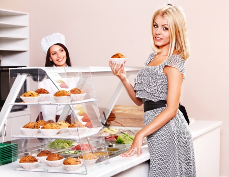 bar counter: Young woman at cafeteria buying food. Stock Photo