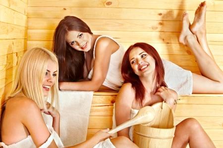 Happy girlfriends relaxing in sauna. photo