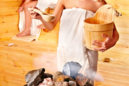 the bather: Women pouring water on rock in sauna.