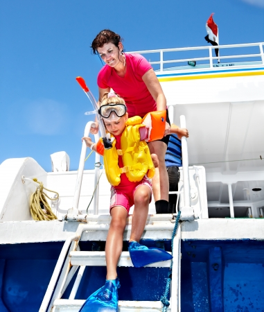 Happy family with child on yacht. Snorkeling travel. photo