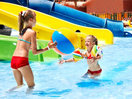 aquapark: Little girl on water slide at aquapark. Stock Photo