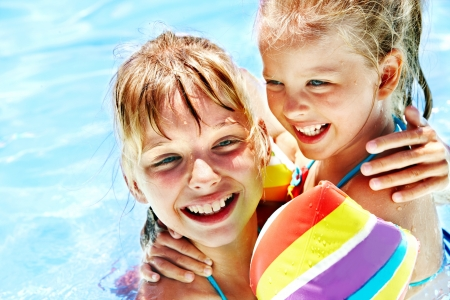 pool fun: Children with armbands in swimming pool.