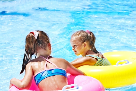 one piece swimsuit: Children sitting on inflatable ring in swimming pool.Rear view. Stock Photo