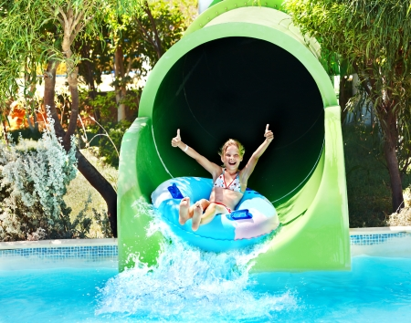 swimming suit: Child on water slide at aquapark. Summer holiday.