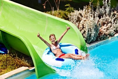 child bikini: Child on water slide at aquapark. Summer holiday.