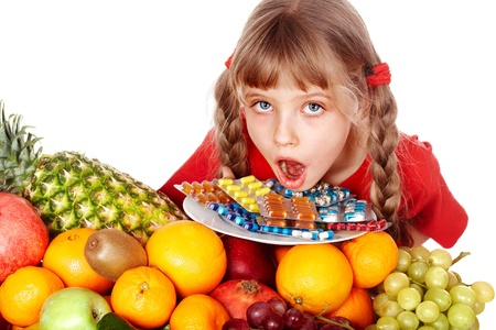 flue season: Child with fruit and vitamin pill. Isolated. Stock Photo