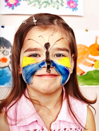 painting face: Child with  face painting in play room. Preschooler. Stock Photo