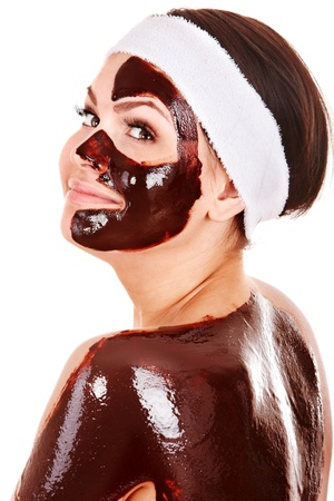 Young woman having chocolate facial mask. Isolated. photo