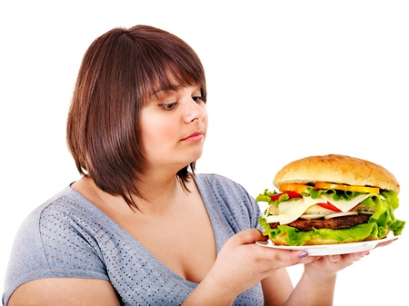 fatty food: Overweight woman eating hamburger. Isolated.