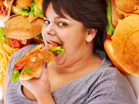 hambriento: Mujer con sobrepeso sosteniendo una hamburguesa.