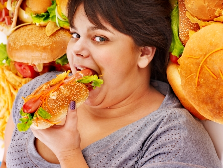 or hungry: Overweight woman holding hamburger.