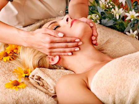 facial treatment: Woman getting facial massage in tropical spa. Stock Photo