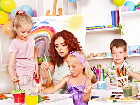 kids club: Child with teacher painting at easel in school. Stock Photo