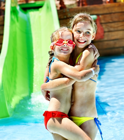 child in bikini: Children on water slide at aquapark. Summer holiday. Stock Photo