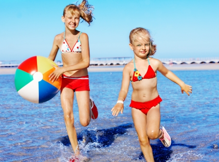 Happy children with beach ball running on  beach. photo