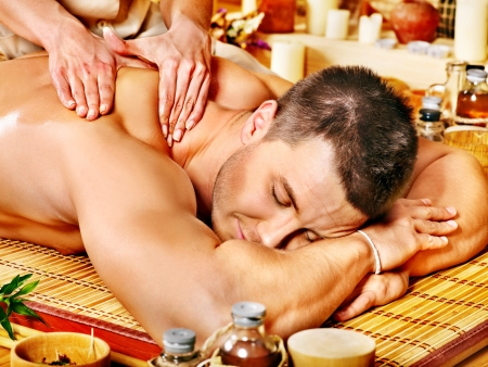 male massage: Man getting massage in bamboo spa. Female therapist.