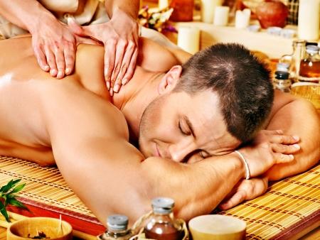 woman massage: Man getting massage in bamboo spa. Female therapist.