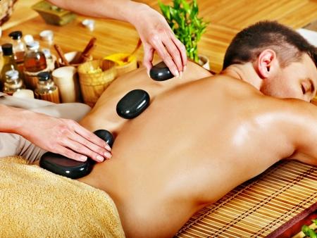 massage homme: L'homme se massage massage aux pierres dans le spa de bambou.