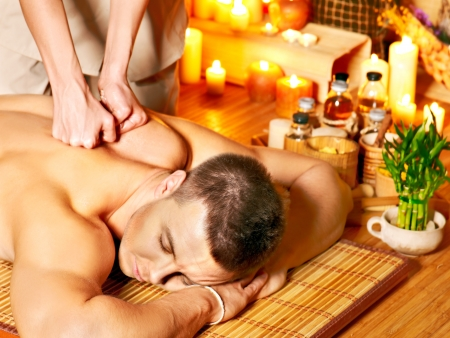 Man getting aroma massage in bamboo spa. Stock Photo