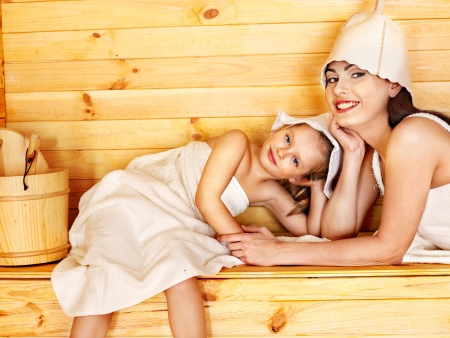 towel  spa  bathroom: Happy family with child relaxing at sauna. Stock Photo