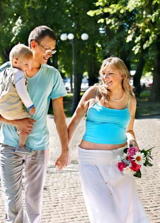 Pregnant woman  with family outdoor in park. Stock Photo - 20635301