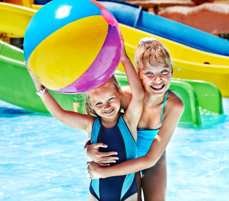 kids playing water: Little girl on water slide at aquapark. Stock Photo